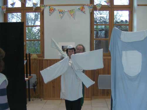 Moulin à vent symbolisé par quatre draps blancs et animé par deux acteurs pendant la répétition de Quichotte et quichotteries
