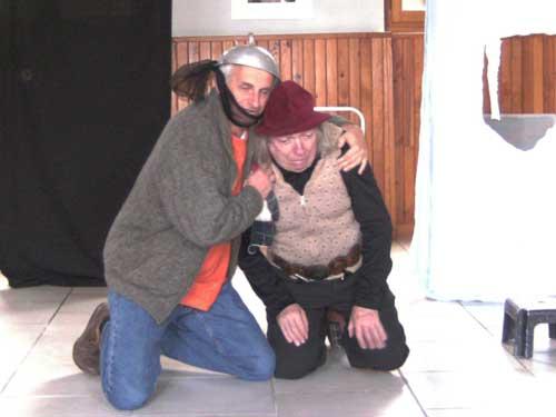 Un acteur à genoux avec un saladier sur la tête en console un autre également à genoux pendant une répétition