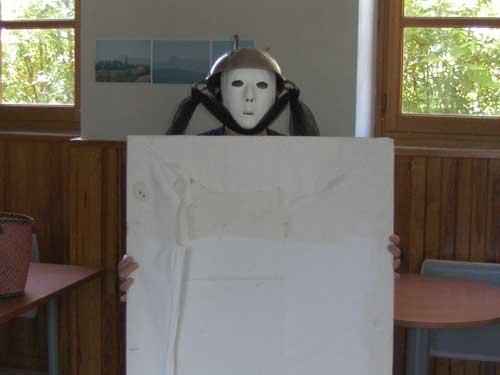 Pendant une mise enscène de Loula Delgado : un acteur avec masque neutre et un saladier su la tête tient un carton blanc devant lui.