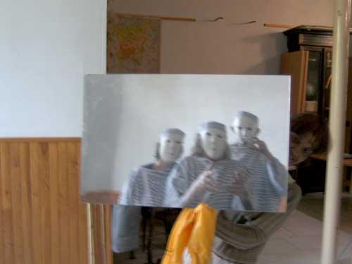 Loula Delgado tenant une photo de trois acteurs avec msque neutre devant elle.