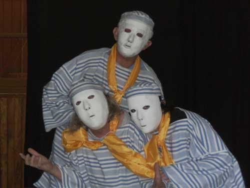 Mise en scène de Loula Delgado pour Quichotte et quichotteries : trois acteurs avec masque neutre, foulard jaune brillant autour du cou et chemise à rayures